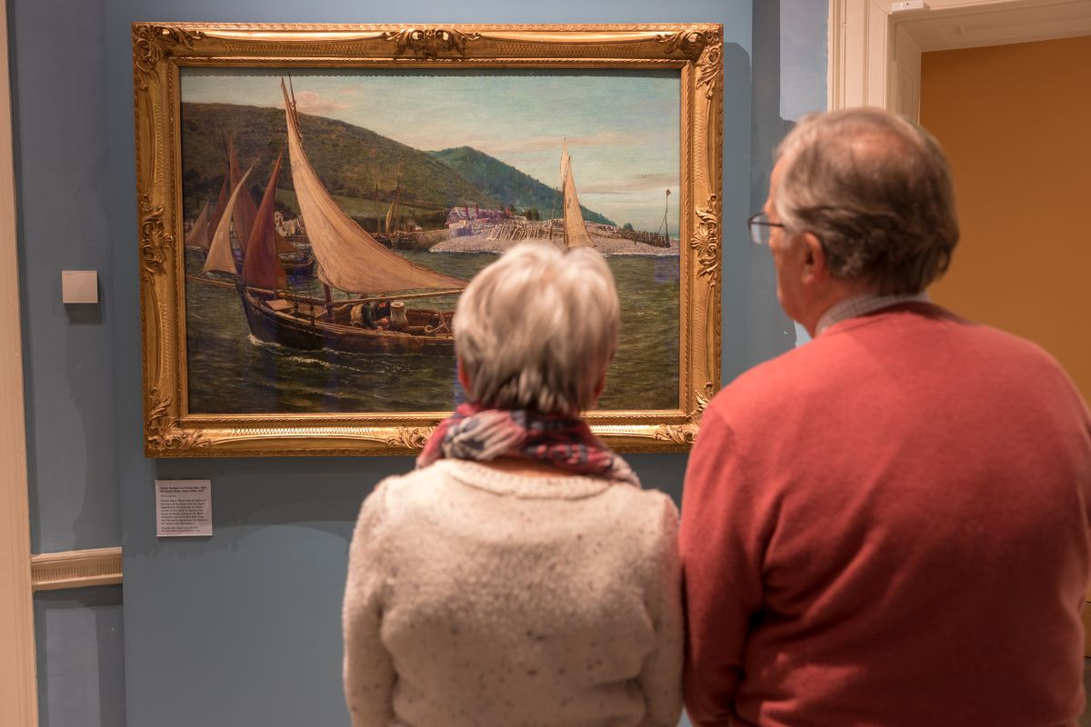 Visitors looking at painting