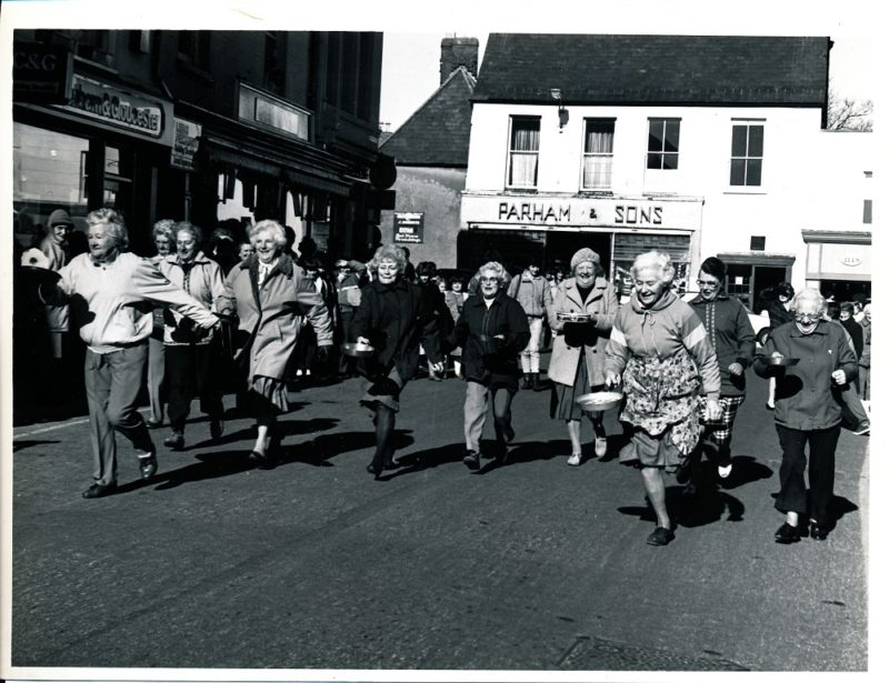 Elderly Women running down a street carrying pans