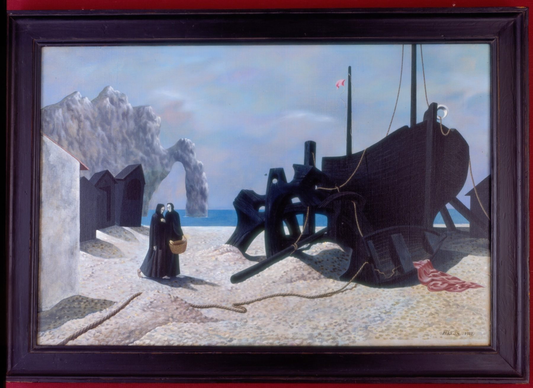 The large hulk of a black ship is shown on a sandy beach. Ropes cascade from its interior, connecting it to a small capsized rowing boat, from which a pink cloth is draped. To the left are two figures dressed floor length in black robes, one of them carrying a basket. Behind them are three black beach huts. The sea, a rocky cove and a cloudy blue sky form the background to the scene.