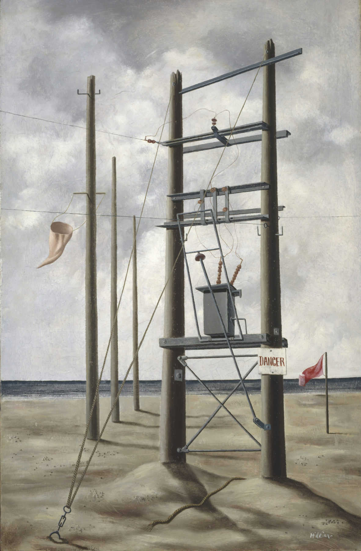 A grey-beige electricity pylon consisting of two wooden columns and metal slats is shown on a sandy beach. A grey box with wires protruding sits on one of the slats, and a danger sign has been affixed to the right column. Three smaller columns rise behind, one with a white flag blowing in the wind. A gloomy grey sky provides the background to the image. A grey-blue strip of sea is between the sand and sky.