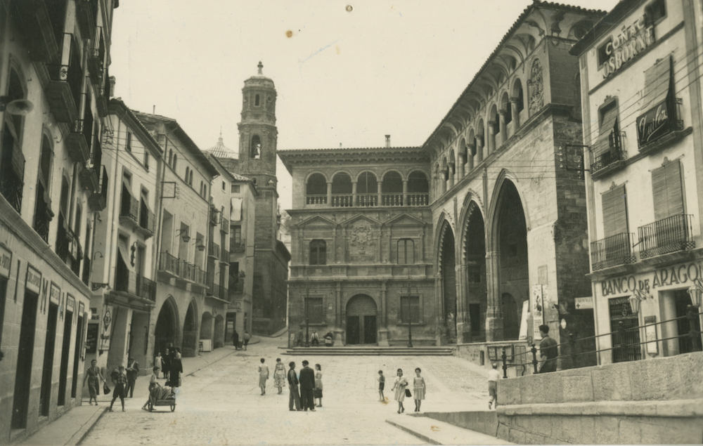 A black and white photograph of a town square with tall baroque buildings and a small grouping of people at the centre.